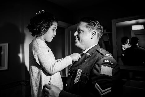Black and white photo of dad and daughter. Father is in military uniform. Daughter is adjusting father's tie. Reflection is visible in mirror.