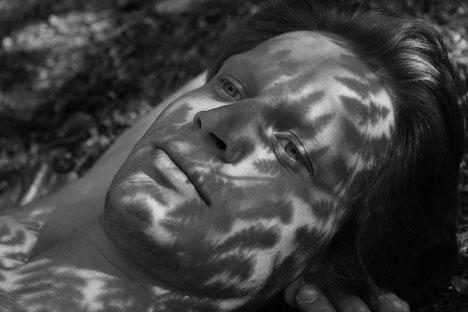 Schwarz Weiss Portrait Fotografie mit Farn Schattenwurf auf dem Gesicht einer Person die im Wald liegt