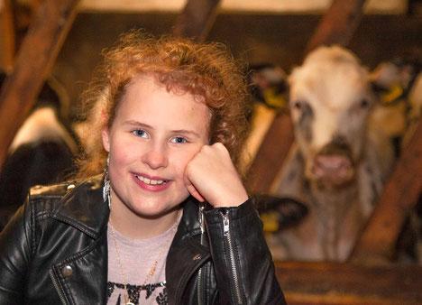 junge Frau auf einem Bauernhof, im Kuhstall, Porträt mit Kuh im Hintergrund