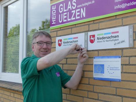 Thorsten Neumann, Inhaber von Heideglas Uelzen, befestigt die neue Kennzeichnung am Firmengebäude.