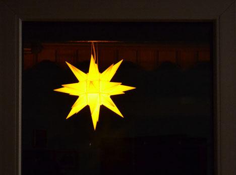 Herrnhuter Stern vor einem Fenster