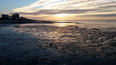 Im Sonnenuntergang im Watt spazieren gehen