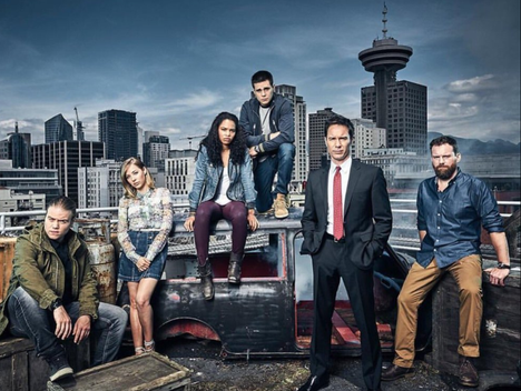 Cast shot of the Vancouver shot TV show Travelers.  Image is of the entire cast outdoors with city skyline in background.