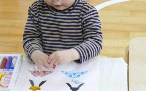 モンテッソーリ活動で、和紙と色紙を使ったひな人形の製作で、1歳児がクレヨンで目と口を書いています。