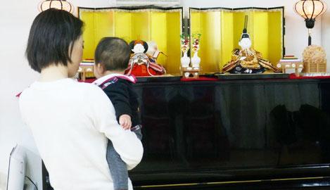 京人形師の祖父が考案したおぼこびなは、小さな子供をイメージした丸い顔とふっくらした胴が特徴的。教室に通うお母様が、「同じ顔だね。」とお子様に語りかけています。