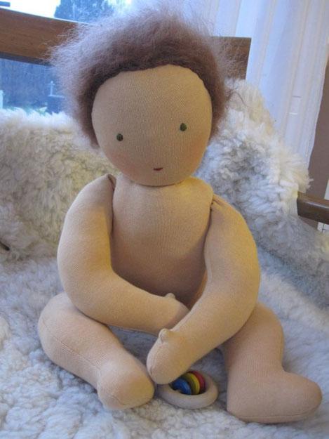 Baby Nicholas hat braunes Flaumhaar und grüne Augen