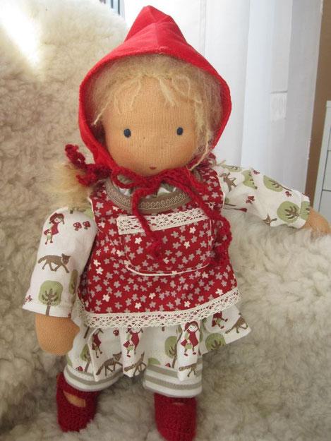 Hannas Püppchen ist bekleidet mit einem Kleid aus dem besonderen Rotkäppchen-Stoff, einer Schürze in rot mit Spitze, einer Ringelleggings (alles Bio-Stoffe), gehäkelten Ballerinas aus Alpaka und natürlich dem roten Käppchen ;-)