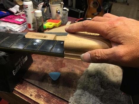 新しいギターネックの指板を調整している作業