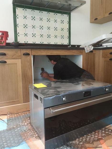 Thierr BESANCON, électricien qualifié, entrain de brancher un four électrique lors de la rénovation d'une cuisine