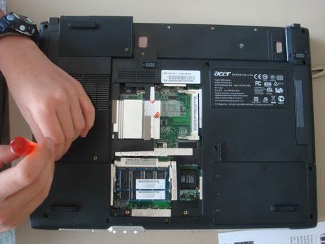 Kind öffnet mit Schraubenzieher einen Laptop