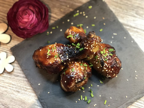 Honig-Sesam Hähnchen auf einer Schieferplatte angerichtet und mit Sesam bestreut