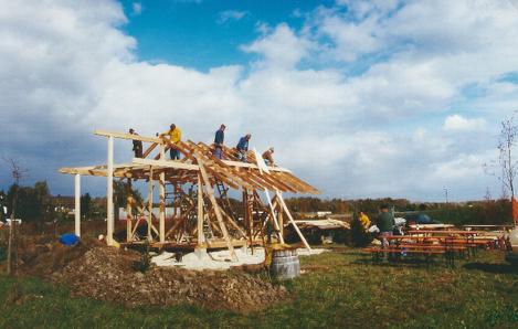 Fünf Arbeietr auf dem Dach warten auf Baumaterial.