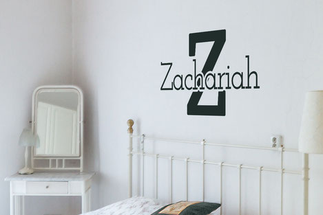 Zachariah vinyl decal personalised name over a bed in a bedroom. Various colours and sizes from www.wallartcompany.co.uk