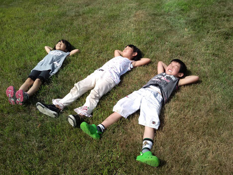 芝生の上に寝転ぶ子どもたち(2011年・北海道にて)