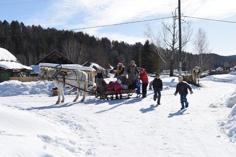Kinder werden mit dem Schlitten zum Gottesdienst gebracht.