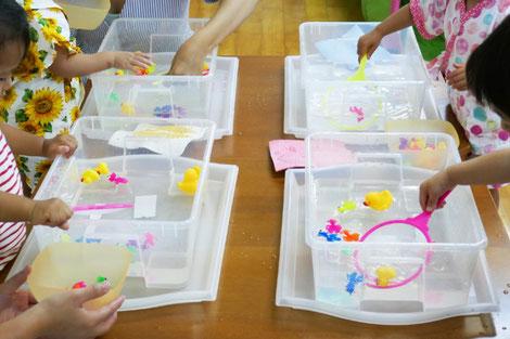 夏祭りの個別活動の金魚すくいコーナーで、生徒が網を使って、模型の金魚やあひるを上手にすくっています。