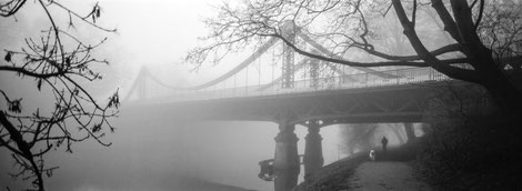 Foggy scene with a bridge over the river.
