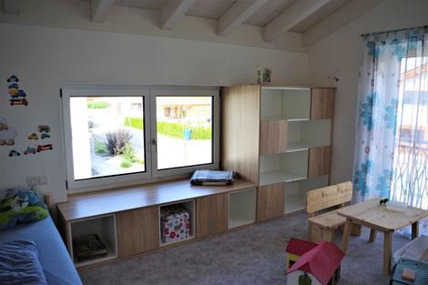Ein Regal mit unterschiedlichen offenen und durch Türen geschlossenen Flächen bietet viel Stauraum für alle Kinderschätze.