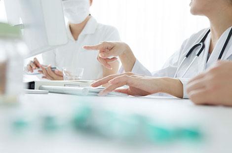 医療機関向けカウンセリング:PCを見ながら打合せをする医療職のスタッフ