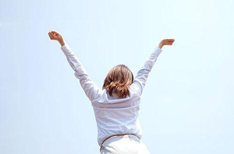 個人向けカウンセリング:両手を伸ばし背伸びしているオフィスレディ風の女性の後ろ姿