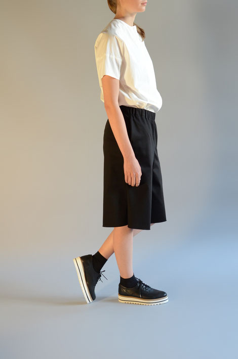 ASCK schwarzer Hosenrock mit Seitentaschen aus Baumwoll-Satin. Der Stoff ist aus kontrolliert biologischen Anbau und GOTS-zertifiziert.