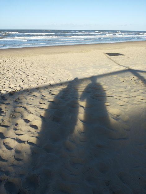 Welche Fußstapfen könnten mal meine werden? Welche Eindrücke will ich hinterlassen? Zu sehen sind 2 Schatten von Menschen, die auf Strand mit vielen Fußeindrücken schauen, im Hintergrund das Meer.