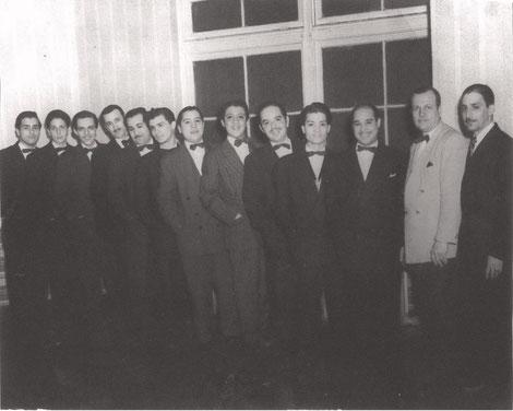 Charlie Palmieri, primero a la izquierda y Charlie Figueroa octavo de izquierda a derecha, el director de la orquesta Rafael Muñoz de vestido claro, década del 50.