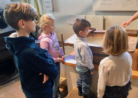 Kinder schauen beim Papierschöpfen zu