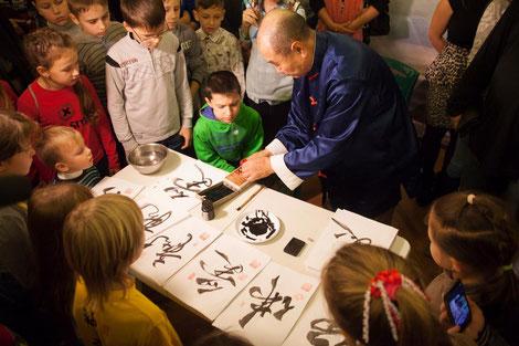 Мастер в окружении детей во время мастер-класса по каллиграфии