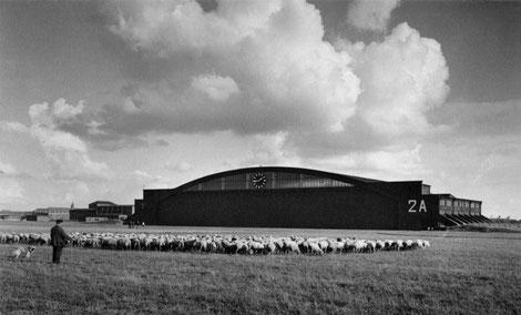 Blick auf die Halle 2A vom Flugfeld aus. Links im Hintergrund die Zellenschlosserei (Flächenbau), kleine Funktionsgebäude sowie Unterkünfte des Fliegerhorstes. Quelle: Peter Binder