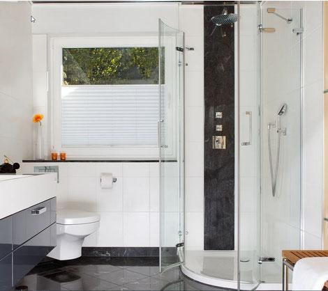 Bad mit halbrunder Duschwanne mit einer Aufkantung von ca. 3 cm kombiniert mit Wandfliesen, Spachteltechnik und einem schwaz-weissem Naturstein