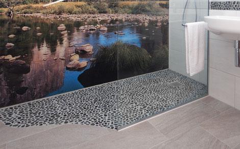 Duschbereich mit Natursteinmosaik kombiniert mit Wand- und Bodenfliesen und einem Urlaubsfoto hinter Glas