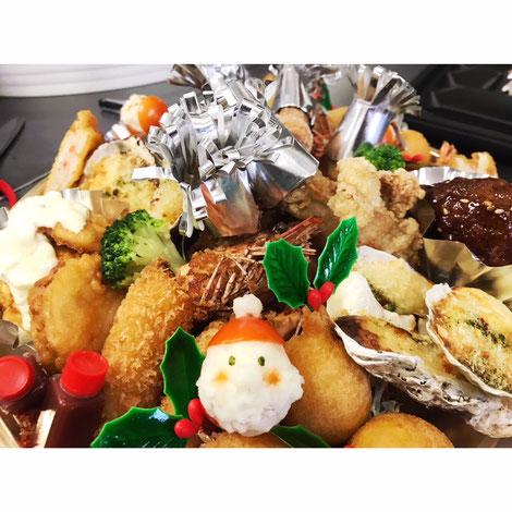 クリスマスオードブルの写真。牡蠣グラタンやチキン南蛮などが入っている。ミニトマトとマッシュポテトでできた可愛いサンタさんが乗っている。