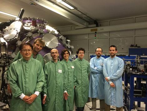 フランスで実施した共同実験にて。後ろの紫色の丸い球が実験装置、左端が福田先生。