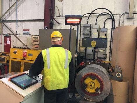 Heizstrahler für Mitarbeiter an einer Maschine in Fabrikhalle