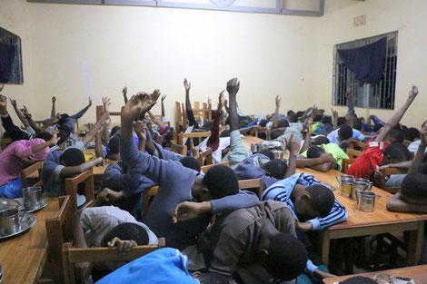 Anonyme und schnelle Wahl: Schülerinnen und Schüler legen den Kopf auf den Tisch, damit niemand die Abstimmung der anderen sieht.