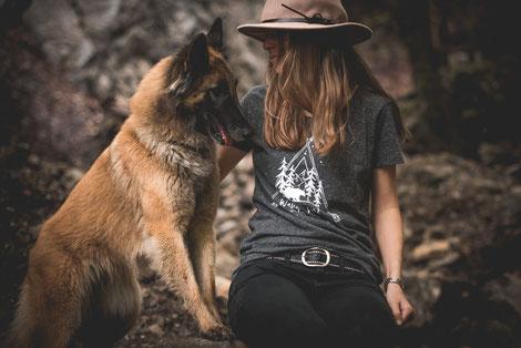 Halterin mit Schäferhund sitzet auf einem Felsen un dträgt ein graues T-Shirt von Wanderrute Adventure store mit einem Abenteuer Druck auf der Vorderseite
