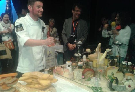Fabien Degoulet devant son œuvre « signée à l'AOP Sainte-Maure de Touraine ». Les deux demi-fromages au sommet de la présentation.  Souces Nouvelle République