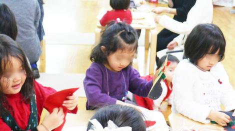 幼稚園児のクリスマス会で年中の生徒が、テープ通しや縫いさしの活動を上手にして、靴下を製作しています。