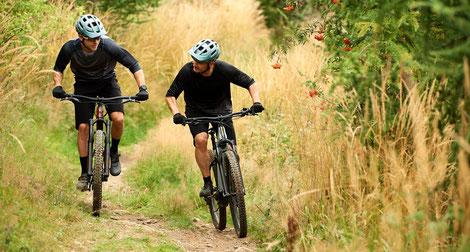 Zwei Männer auf e-Mountainbikes von Giant mit Helmen