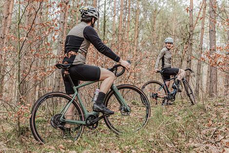 Ein Mann und eine Frau auf unbefestigtem Waldweg auf den Specialized top Gravel e-Bike Modellen