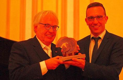 Kulturdezernent Thomas Schmitt (rechts) überreicht Hermann Lewen den Ehrenpreis der Stadt Trier in Form einer Baumscheibe.