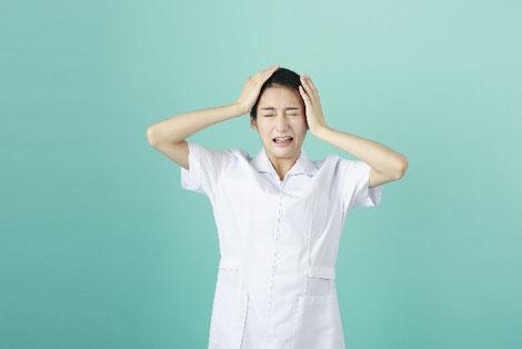 頭を抱える女性薬剤師の画像