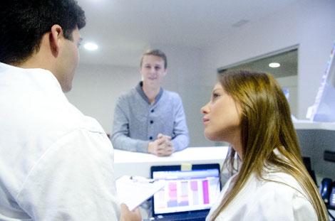 薬局の受付で話をする薬剤師と患者の画像