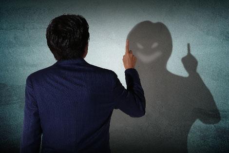 男性の影が悪人の顔になっている画像