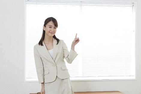 窓際で指をさしている女性薬剤師の画像