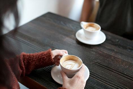 Zwei Personen trinken einen Cappuccino