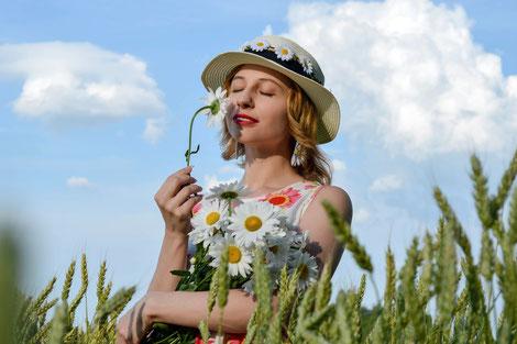 Junge Frau mit Hut auf Blumenwiese