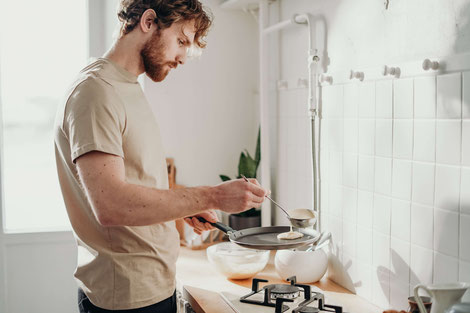 MAN COOKING ALONE IN THE KITCHEN