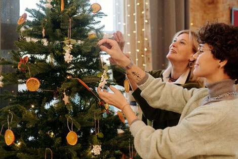 TWO WOMEN HANGING CHRISTMAS ORNAMENTS